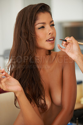 Buy stock photo A young woman being made up by a makeup artist while sitting naked on a chair