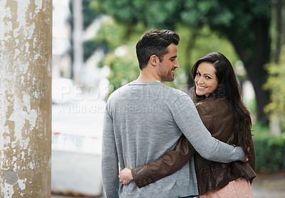 Buy stock photo Shot of an affectionate young couple walking in the street