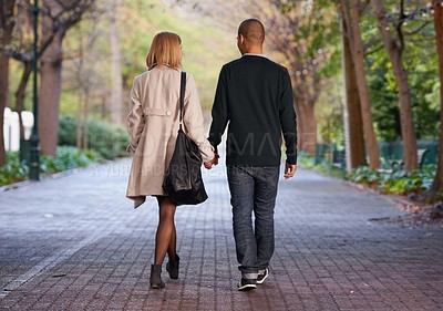 Buy stock photo Full length rearview shot of a young couple walking hand in hand in a park