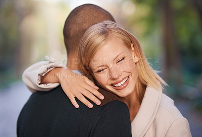 Buy stock photo Shot of a young couple embracing each other in the outdoors