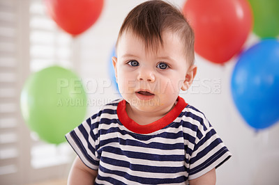 Buy stock photo Shot of a baby boy sitting at home with balloons in the background