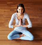 Happy young female exercising yoga with hands joined