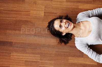 Buy stock photo Joyful young female looking away while lying on fl