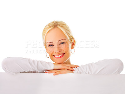 Buy stock photo Studio portrait of a young woman standing behind a blank sign isolated on white