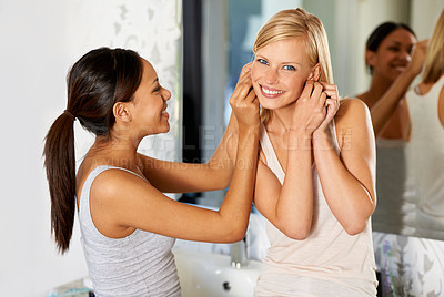 Buy stock photo Shot of a young woman helping her friend to put her earrings in
