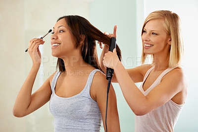 Buy stock photo Shot of a young woman applying makeup while her friend straightens her hair