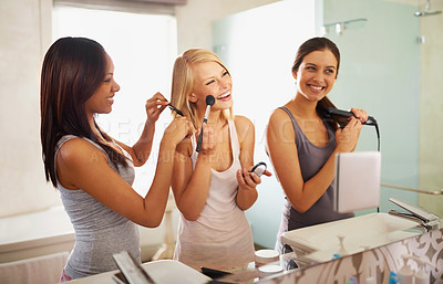 Buy stock photo Shot of three friends applying makeup in front of the mirror