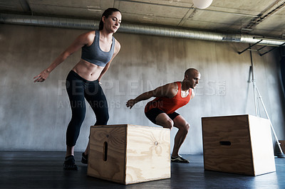 Buy stock photo Shot of a man and woman training together at the gym