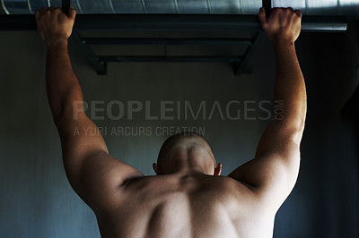 Buy stock photo Shot of a man doing pull-ups at the gym
