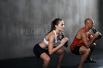 Buy stock photo A man and woman working out with kettle bells at the gym