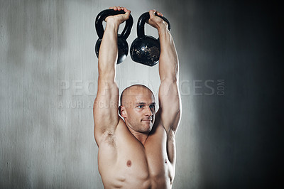 Buy stock photo Shot of a man working out with kettle bells at the gym