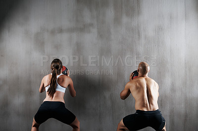 Buy stock photo Shot of a young man and woman working out with medicine balls at the gym