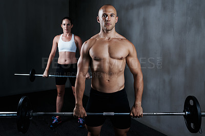 Buy stock photo Cropped shot of a man and woman working out with barbells