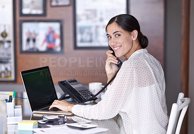 Buy stock photo A young woman talking on the phone while working on her laptop