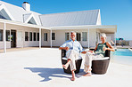Elderly couple enjoying themselves outdoors with their house at the back