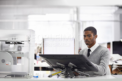 Buy stock photo Cropped shot of a young man working on his computer
