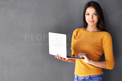 Buy stock photo Portrait of an attractive young woman holding a laptop while standing against a gray wall