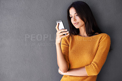 Buy stock photo Shot of an attractive young woman using a mobile phone while standing against a gray wall