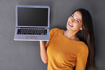 Buy stock photo Portrait of an attractive young woman holding up a laptop with a blank screen