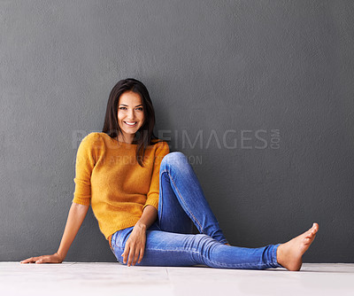 Buy stock photo Portrait of an attractive young woman sitting on the floor against a grey wall