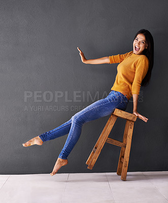 Buy stock photo Portrait of a happy young woman leaning back on a stool