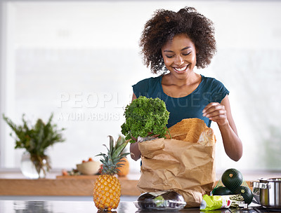 Buy stock photo Cropped shot of a young woman with some groceries