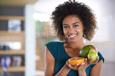 Buy stock photo Portrait of an attractive young woman holding a bunch of different fruit
