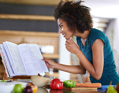 Buy stock photo A young woman cooking from a recipe book