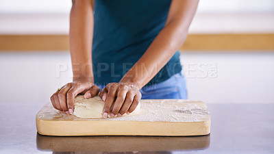 Buy stock photo Cropped shot of a young woman pressing dough