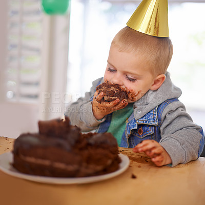 Buy stock photo Cropped shot of a young boy eating his birthday cake before the party