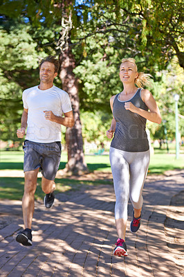 Buy stock photo A couple in sportswear jogging through the park