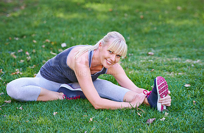 Buy stock photo Shot of a young woman stretching on a grassy field