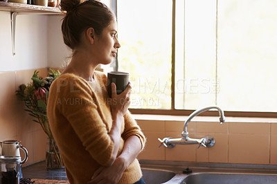 Buy stock photo Attractive young woman in her kitchen having a warm beverage while she looks out of her window