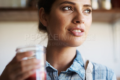 Buy stock photo A beautiful young woman standing indoors and drinking freshly-juiced juice