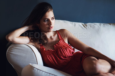Buy stock photo A beautiful young woman lying on the couch with a thoughtful expression