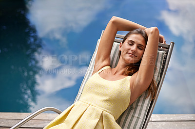 Buy stock photo A pretty woman relaxing on a deck chair with her eyes closed