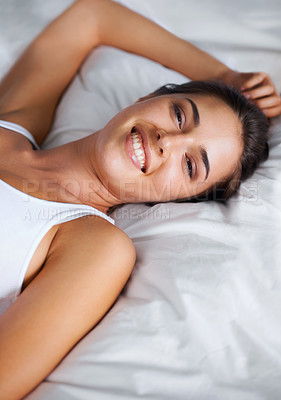 Buy stock photo Portrait of a beautiful young woman relaxing in bed at home