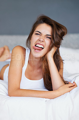 Buy stock photo A young woman pulling faces while lying in bed