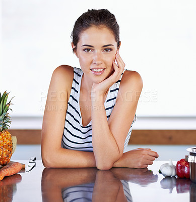 Buy stock photo A portrait of a beautiful young woman leaning on her kitchen counter next to food and a cooking pot