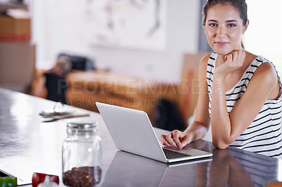 Buy stock photo Portrait of an attractive young woman using her laptop in the kitchen