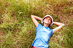 Above view of a cute small girl resting on the grass and looking upwards