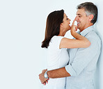 Happy mature couple fondling each other over a white background