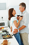 Happy mature couple drinking wine together in the kitchen