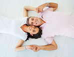 Happy mature couple holding hands and lying down with their heads together
