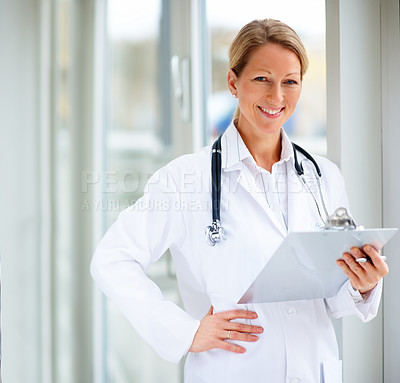 Smiling successful mature female doctor holding a writing pad