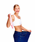 Happy young female in old jeans pant after losing weight and holding measuring tape