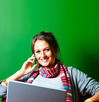 Pretty smiling young woman using a cellphone and laptop on green