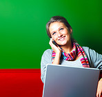 Pretty young woman using a cellphone and laptop on a colorful background