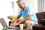 Happy mature man using a laptop at home