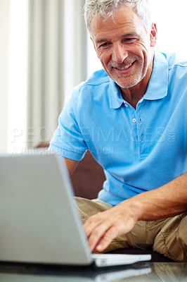 Buy stock photo Handsome senior man working on a laptop